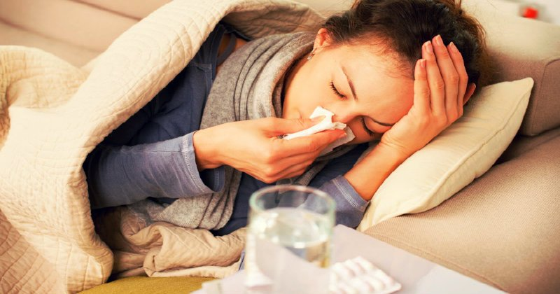 sick woman lying on couch and clearing her nose with tissue