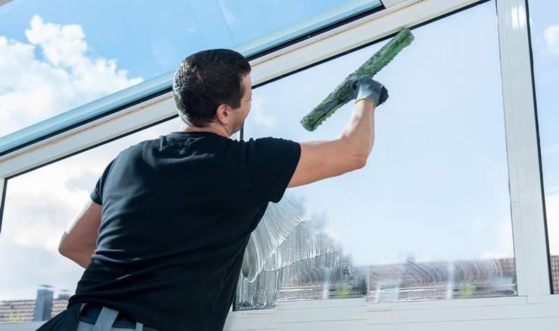 a man is wiping window glass