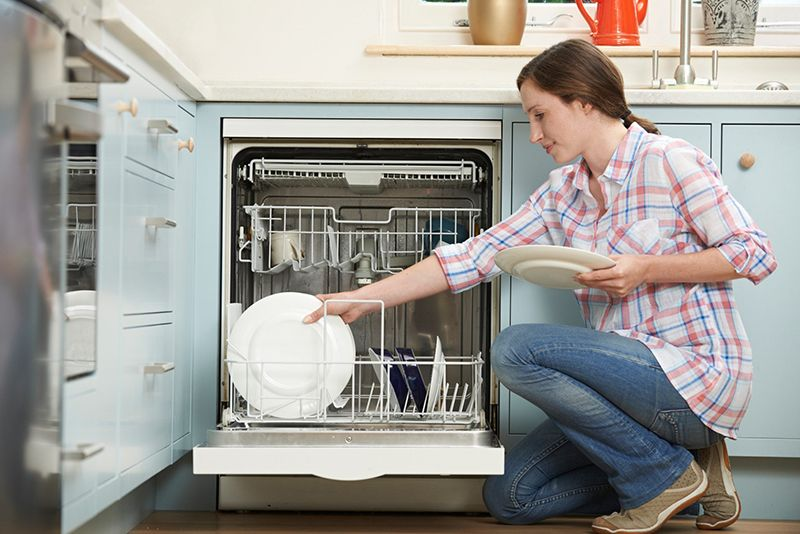 woman doing dishes in a dishwasher