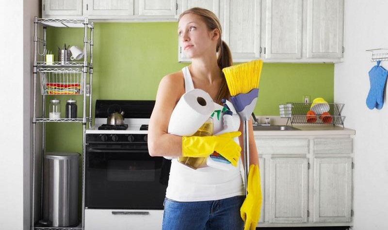 a woman is standing at her kitchen and holding a broom brush