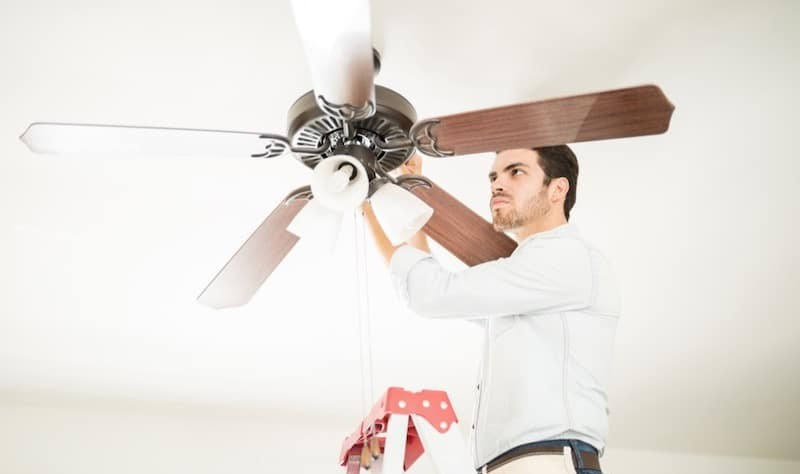 young man trying to fix a ceiling fan
